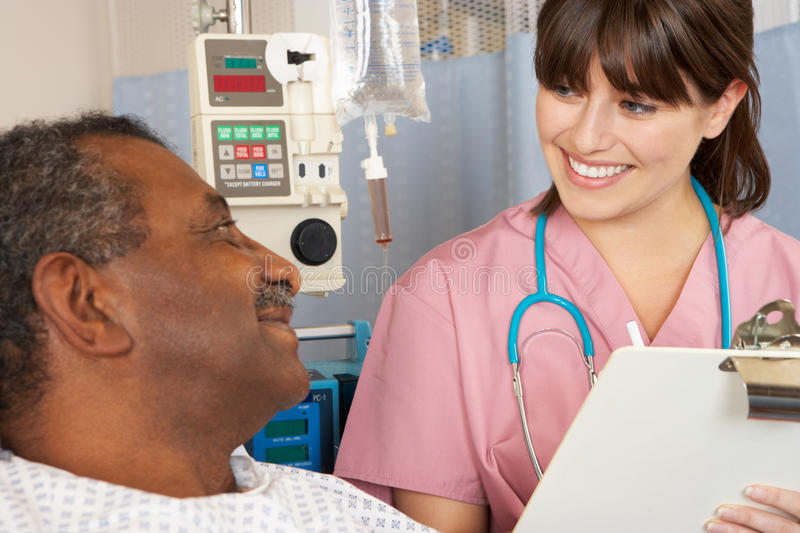Nurse Talking To Senior Male Patient On Ward stock photo