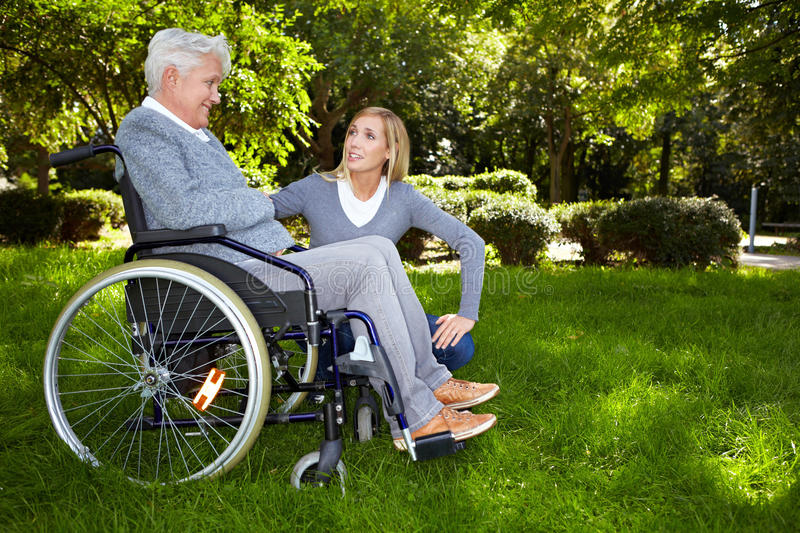 Nurse talking to woman. Young nurse talking to woman in wheelchair in park stock image