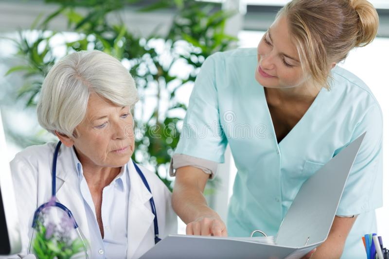 Nurse talking to woman doctor with folder. Nurse talking to women doctor with folder nurse stock images