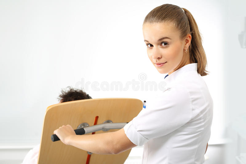 A nurse tends to a patient. Young nurse carries a patient in a wheelchair stock image