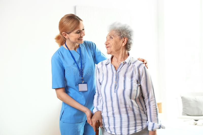 Nurse in uniform assisting elderly woman royalty free stock images