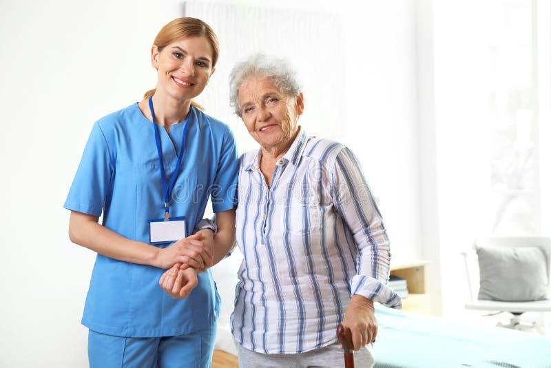 Nurse in uniform assisting elderly woman stock photo