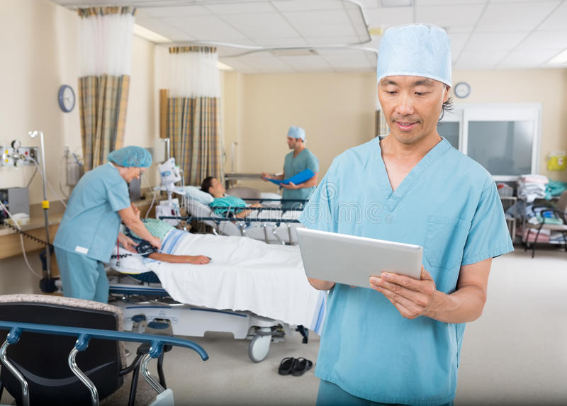 Nurse Using Digital Tablet In Ward stock photography