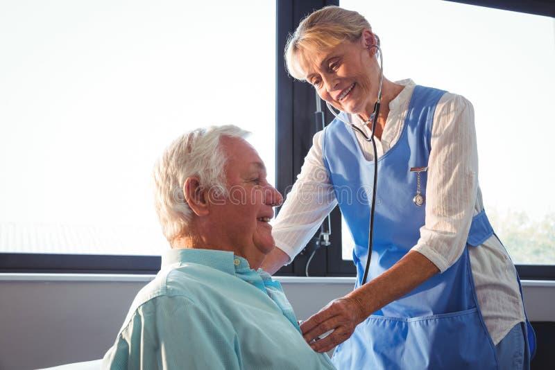 Nurse using stethoscope to take care of a senior man stock images