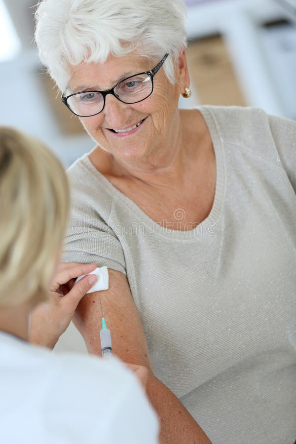 Nurse vaccinating elderly woman. Nurse making vaccine injection to elderly patient stock photography