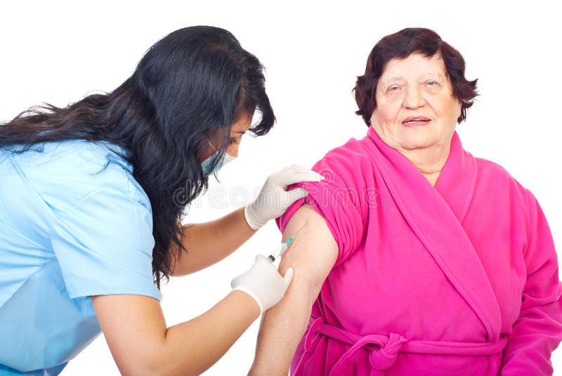Nurse vaccine elderly woman patient. Nurse woman with protective mask and gloves vaccine her elderly woman patient,check also stock photography