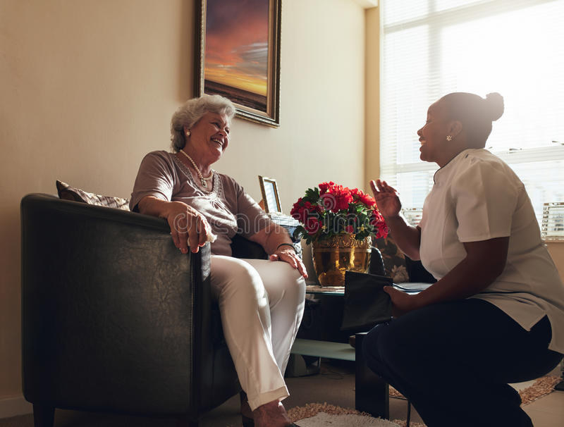 Nurse visiting senior patient home for routine checkup stock images