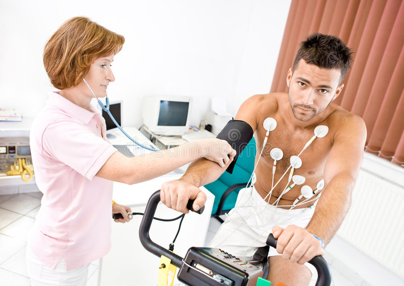 Nurse working. Nurse makes the patient ready for medical EKG test. Real people, real locacion, not a staged photo with models royalty free stock image