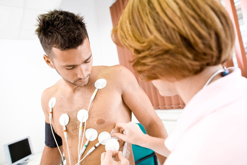 Nurse working. Nurse makes the patient ready for medical EKG test. Real people, real locacion, not a staged photo with models royalty free stock images