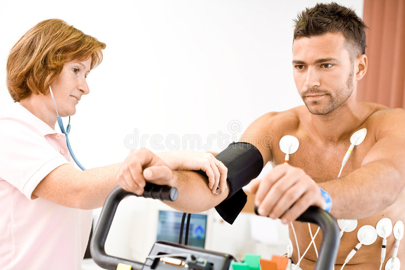 Nurse working. Nurse makes the patient ready for medical EKG test. Real people, real locacion, not a staged photo with models royalty free stock photography