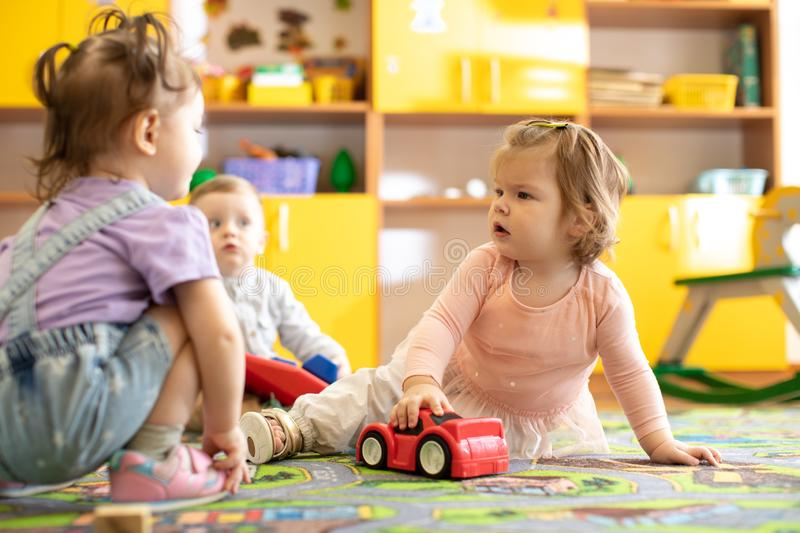Nursery babies girls and boy playing together in a play room royalty free stock photo