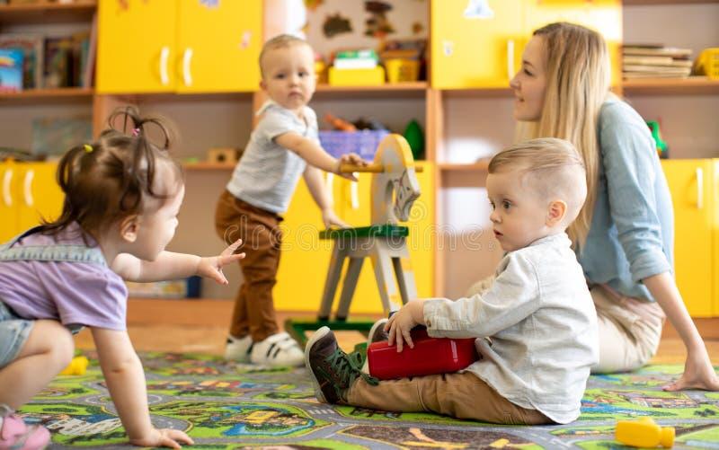 Nursery babies playing in kindergarten stock images