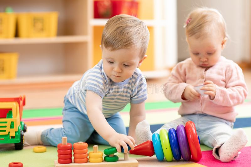 Nursery babies playing with educational toys, early learning royalty free stock photography