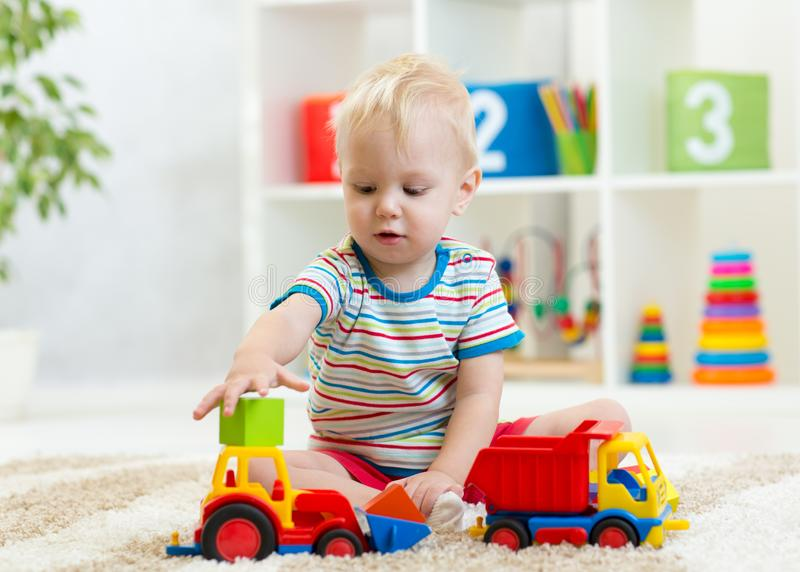 Nursery baby playing with toy cars in kindergarten stock image