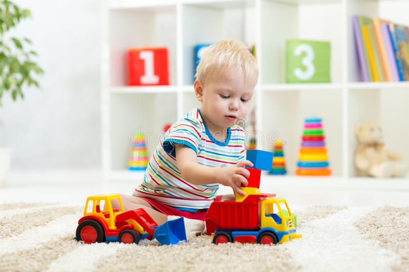 Nursery baby plays block and car toys sitting on carpet indoors. Nursery baby boy plays block and car toys sitting on carpet indoors stock photography