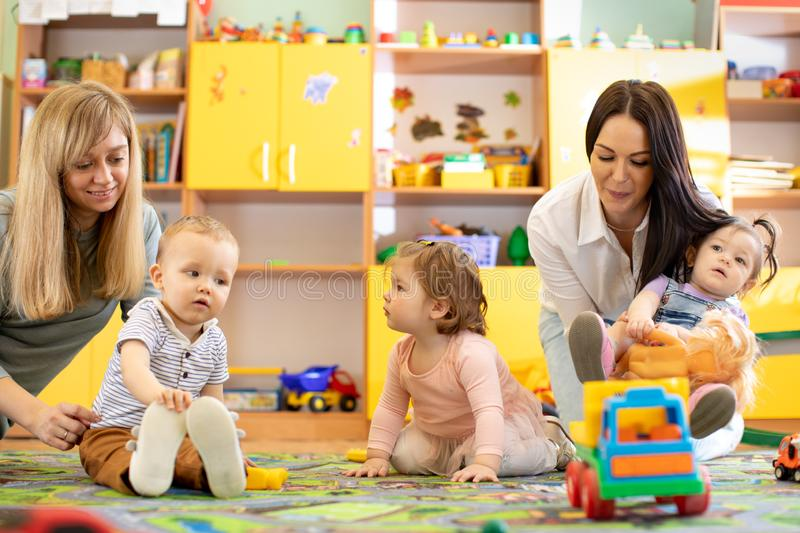 Nursery children playing with teacher and helper in the classroom. Nursery children playing with teacher and helper in kindergarten royalty free stock image
