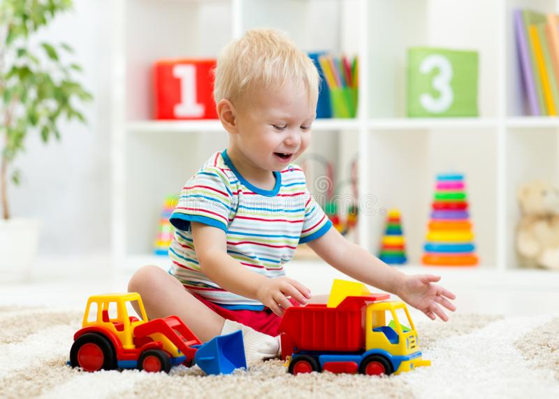 Nursery kid boy toddler playing with toys in kindergarten royalty free stock images