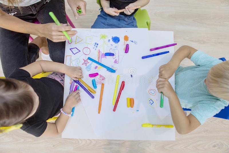 Nursery kids and their teacher drawing with crayons royalty free stock photography