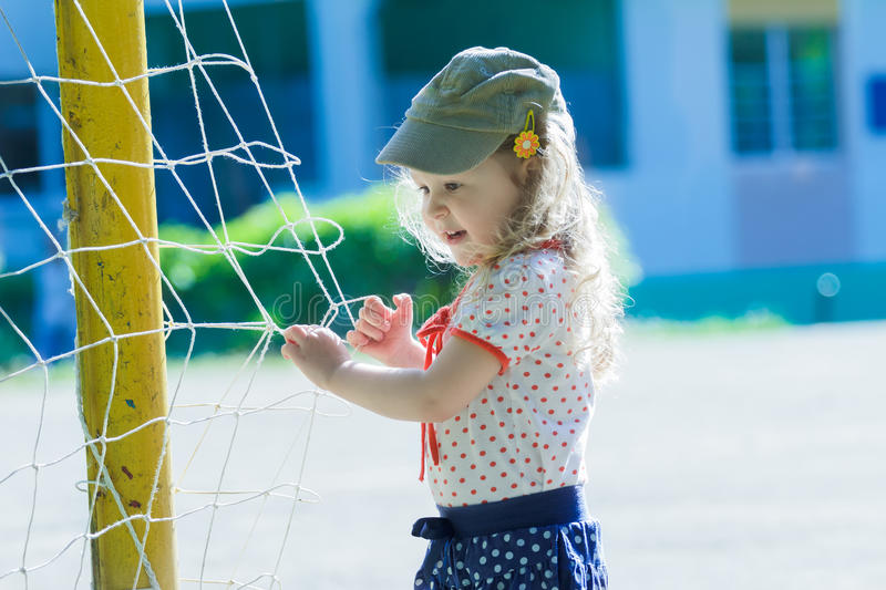 Nursery school girl playing near football goal net with yellow goalposts royalty free stock photo
