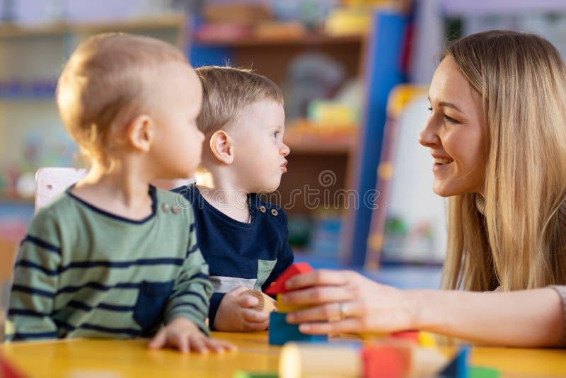 Nursery teacher with cute little children in kindergarten royalty free stock image
