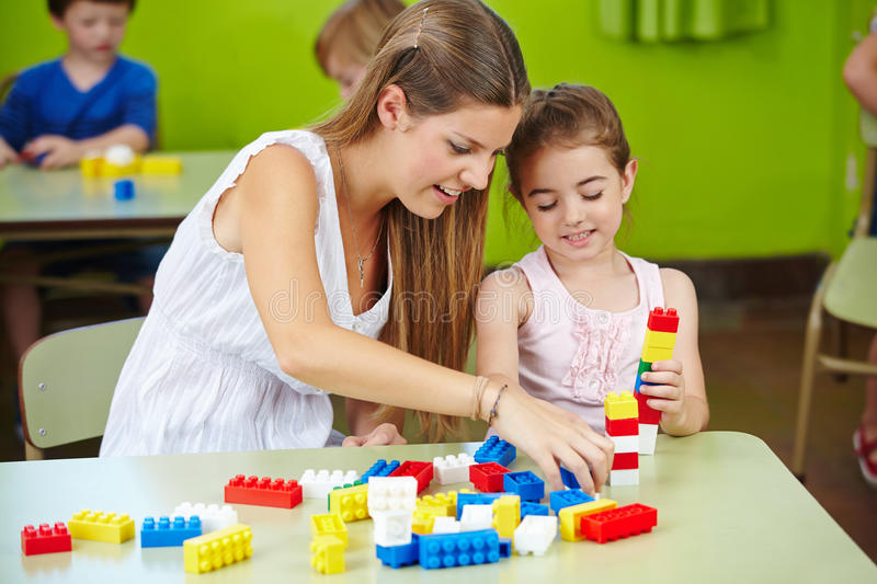 Nursery teacher and girl playing. With building bricks in a kindergarten royalty free stock photos