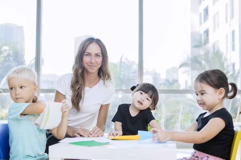 Nursery teacher and her students make paper crafts stock photos