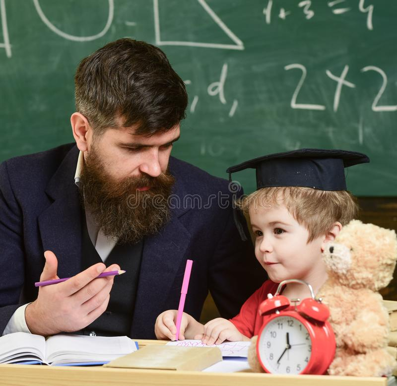 Nursery teacher and little child drawing picture. Teacher in formal wear and pupil in mortarboard in classroom. Chalkboard on background. Father teaches son stock images