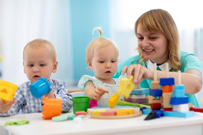 Nursery teacher looking after children in daycare. Little kids toddlers play together with developmental toys. stock photos