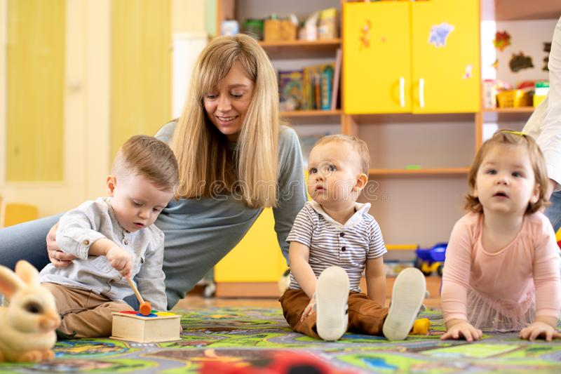 Nursery teacher looking after children in daycare. Little kids toddlers play together with developmental toys. royalty free stock photos