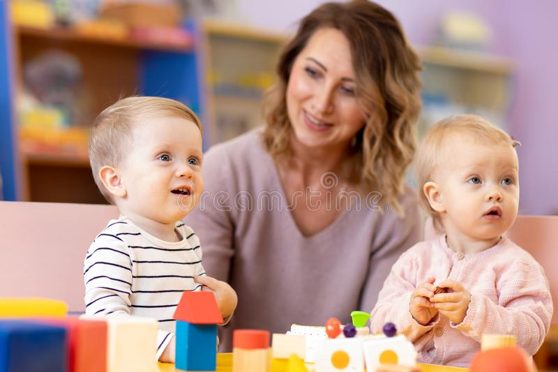 Nursery teacher looking after children in daycare. Little kids toddlers play together with developmental toys stock photos