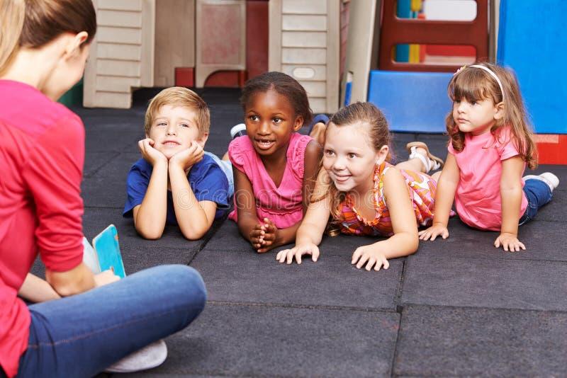 Nursery teacher reading book to group of kids royalty free stock photos