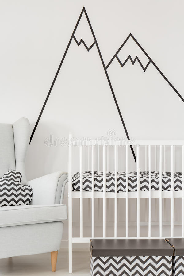 Nursery with white cot. Armchair and decorative wall decal royalty free stock photo