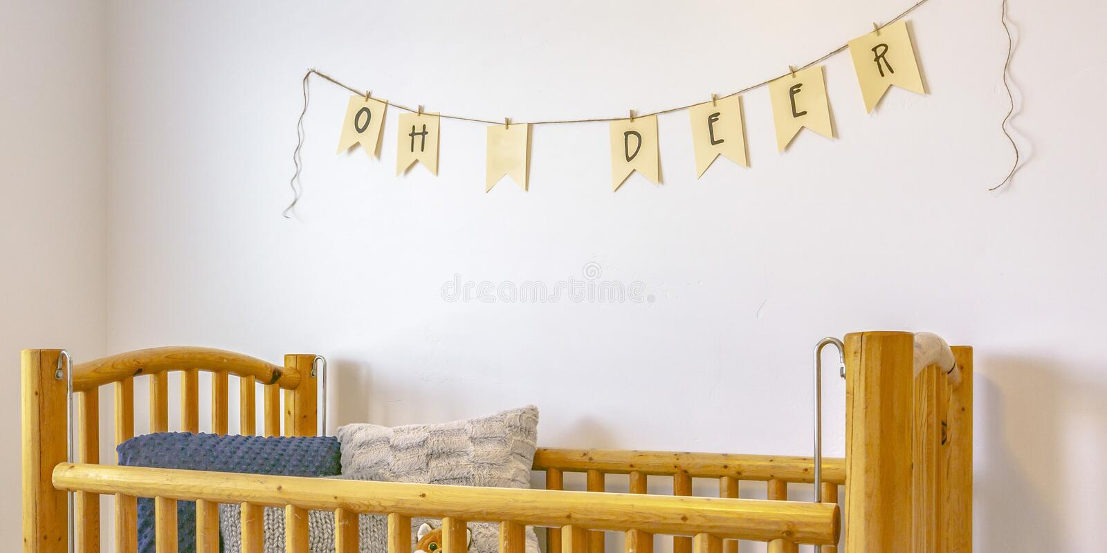 Nursery with wooden crib and bunting on the wall stock photography