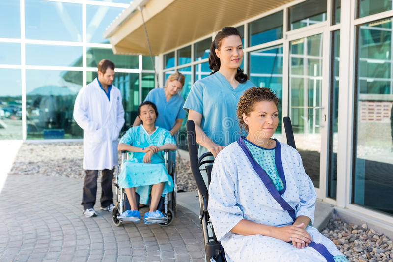 Nurses Assisting Patients On Wheelchairs Outside stock images