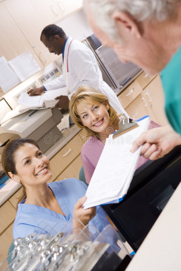 Nurses Being Handed A Clipboard. At The Reception Area In A Hospital royalty free stock image