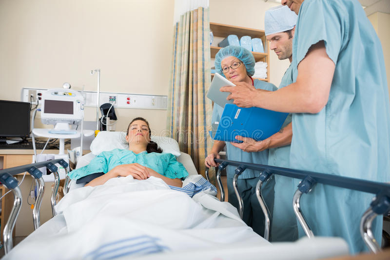 Nurses Discussing Patient's Report By Bed stock photography