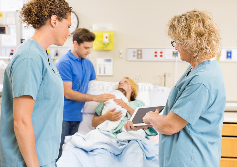 Nurses Discussing Report On Digital Tablet Against stock images