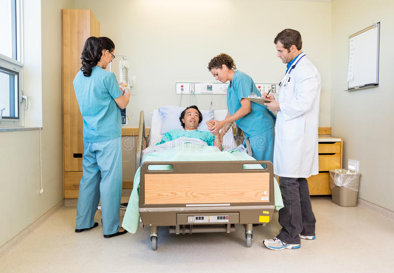 Nurses And Doctor Examining Patient In Hospital royalty free stock image