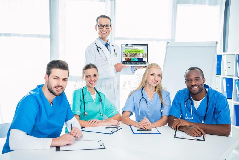 team of male and female nurses and general practitioner with laptop royalty free stock photos
