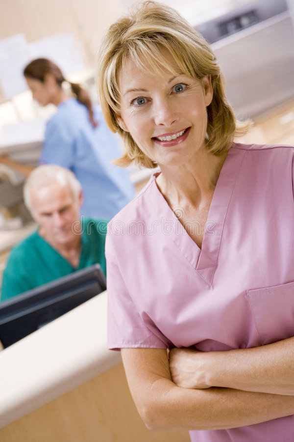 Nurses In The Reception Area Of A Hospital. With one nurse looking to camera stock photography