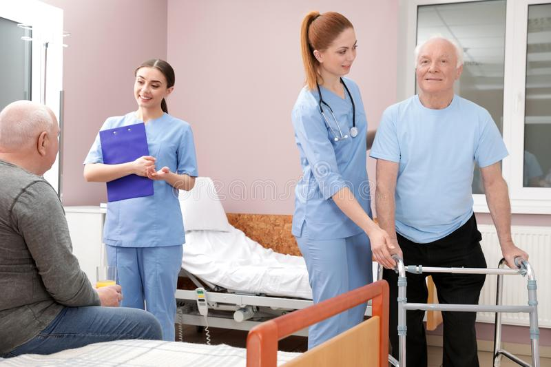 Nurses with senior patients in hospital ward. Medical assisting royalty free stock photography