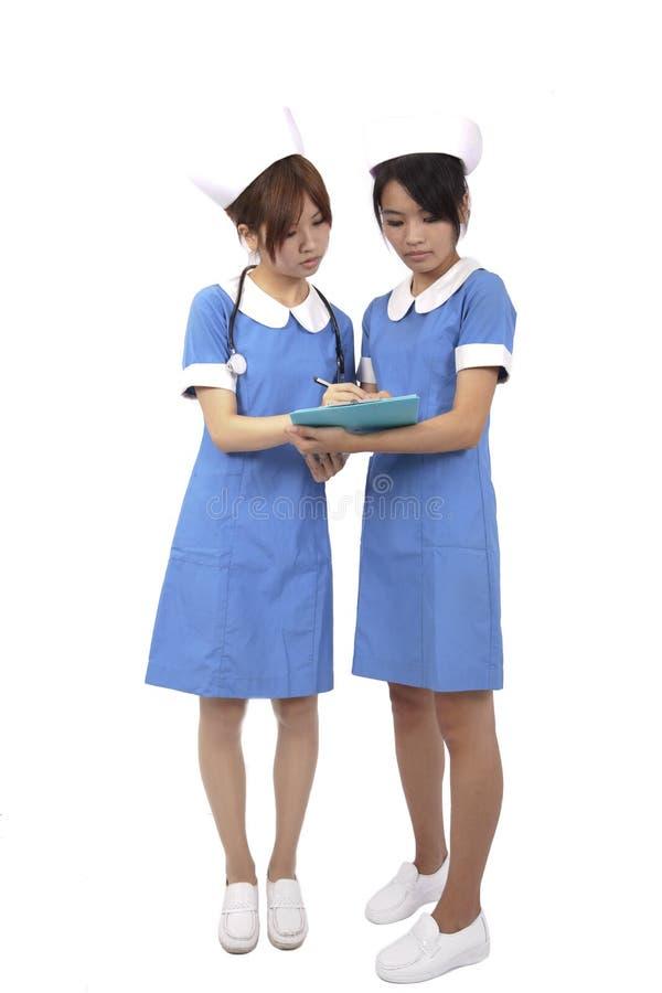 Nurses team reading on clipboard royalty free stock photography