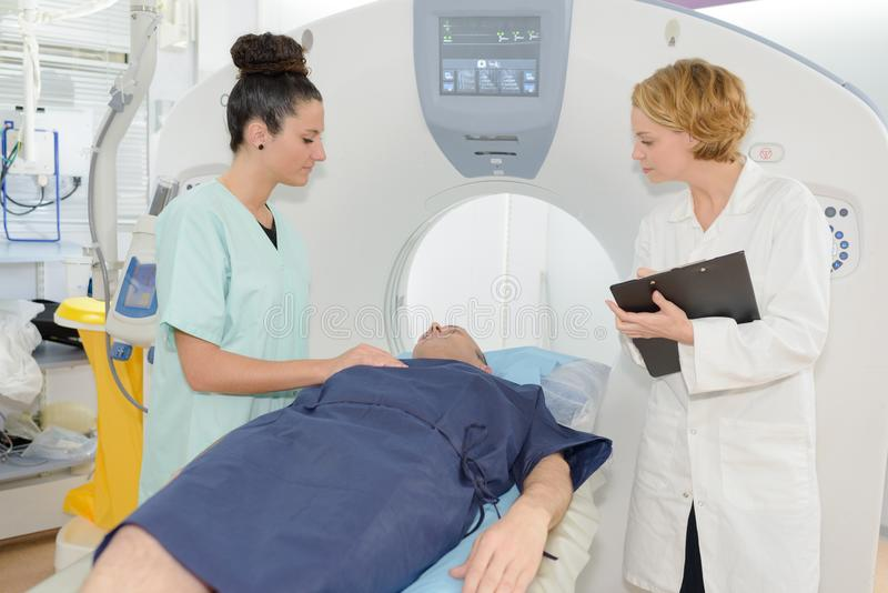 Nurses about to perform tomography on male patient royalty free stock image