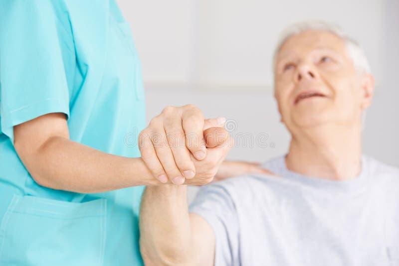 Nursing assistant holding hand of senior man stock image