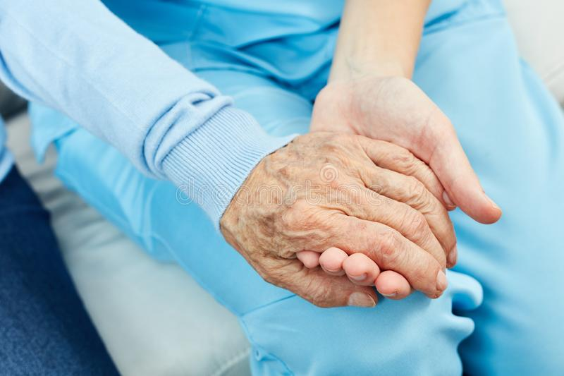 Nurse holds hand of a senior citizen stock photo