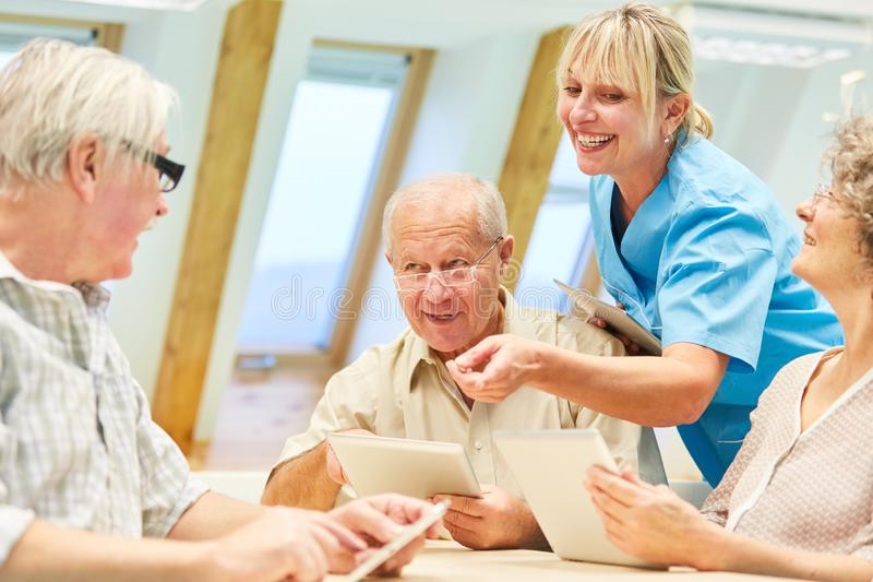 Nursing help is fun with seniors in the computer course royalty free stock photos