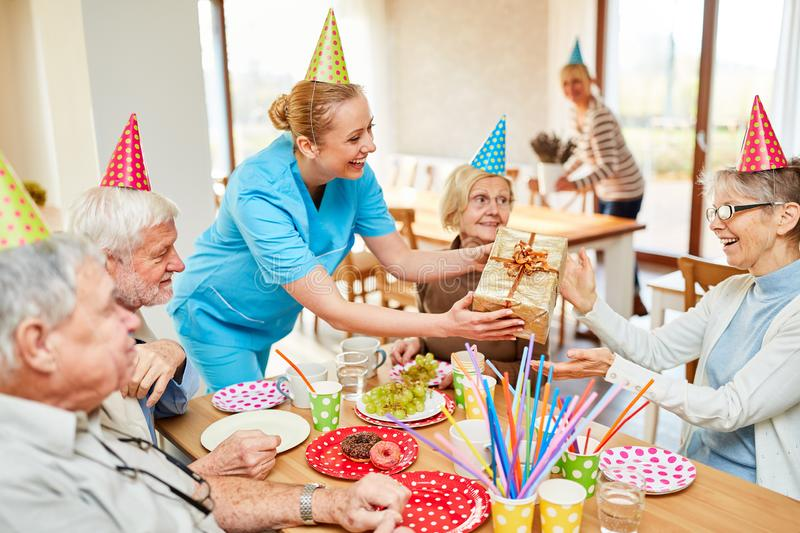 Young nursing assistant gives a present to elderly woman royalty free stock photos