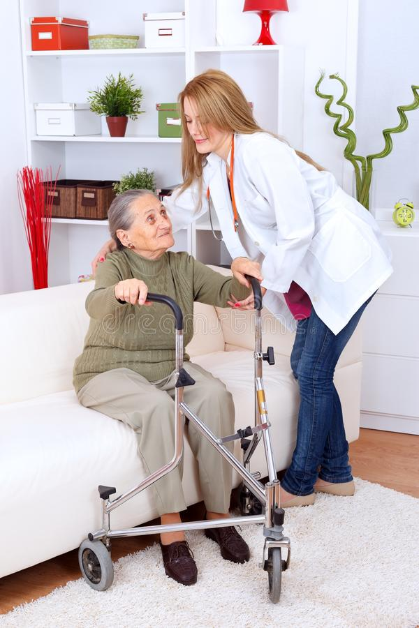 Nursing home care. Nurse helping elderly woman with walker at home