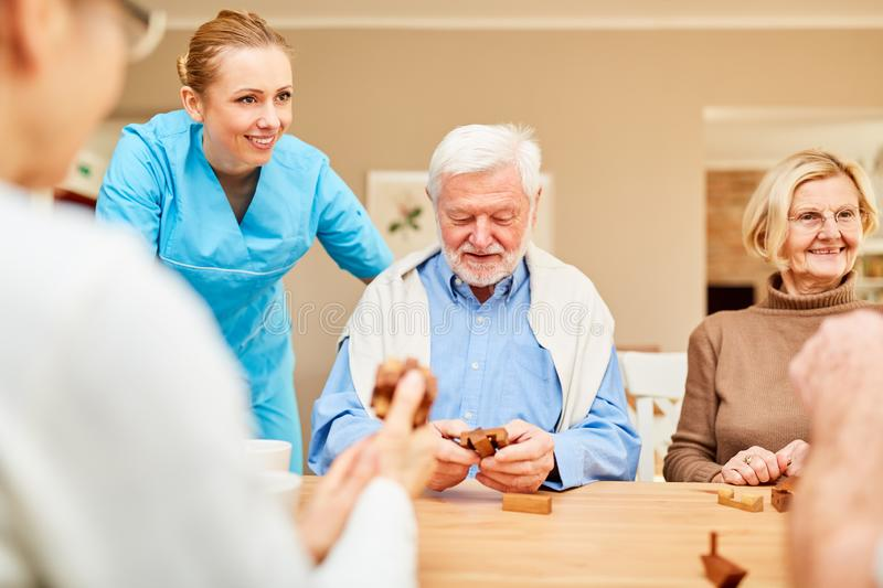 Nursing home care for seniors with dementia. Nursing home care for seniors group with dementia in the puzzle game with wooden puzzle royalty free stock photos
