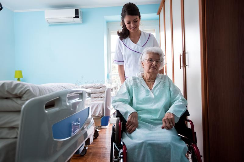 Nursing home, nurse goes outside with old woman at wheelchair royalty free stock images